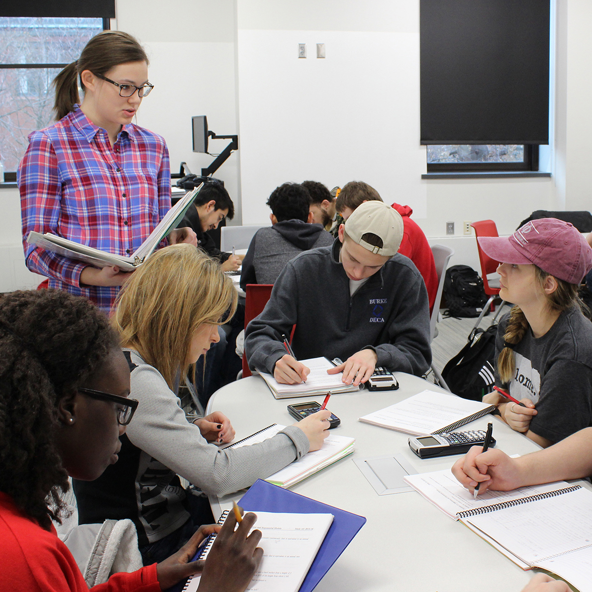 Undergraduate learning assistant Meredith Hovis (left), a secondary mathematics (6-12) major, facilitates group discussions with students in a Math 101 course