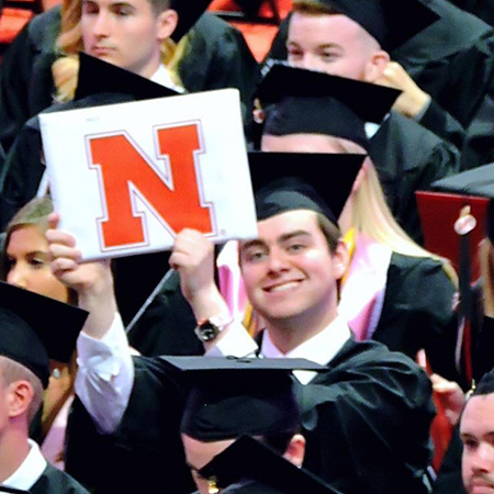 Lawrence Seminario holds up his diploma at UNL graduation.